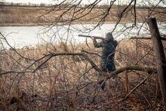 Jägareman med det förberett vapnet som siktar och att göra ett skott under jakt royaltyfri bild