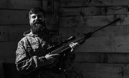 Jägaren den brutala hipsteren med vapnet förbereder geväret för att jaga, kopieringsutrymme Huntsmanbegrepp Mannen med skägget bä royaltyfri fotografi
