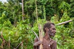 Jägaren för ståendeKorowai man med pilen och pilbågen Stam av Korowai (Kombai, Kolufo) Royaltyfria Bilder