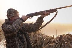 Jägaren skjuter ett vapen på gryning arkivbild