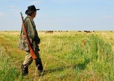 Jäger, der auf das Grasland geht stockbilder