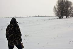 Jäger, der auf das schneebedeckte Feld im Winter geht stockfoto
