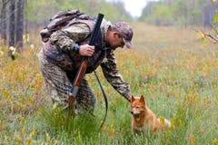 Jäger, der den Hund streicht Stockbild