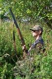 Jäger, der im hohen Gras sich versteckt Stockbild
