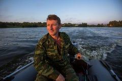 Jäger in der Tarnung fährt ein Motorboot auf dem See liebhaberei lizenzfreie stockfotografie