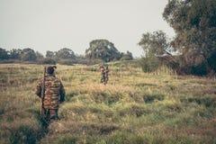 Jäger, die durch hohes Gras auf dem ländlichen Gebiet während der Jagdsaison kreuzen Stockbild