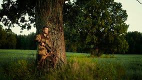 Jäger liegt auf einem Gebiet und bereitet vor sich zu schießen stock video
