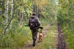 Jäger mit dem Hund, der auf den Waldweg geht stockfoto