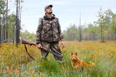 Jäger mit einem Gewehr und einem Hund auf dem Sumpf Lizenzfreie Stockfotos