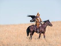 Jäger mit einem goldenen Adler Getrocknet herauf Hügel stockfotografie