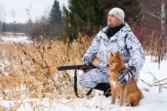 Jäger mit Gewehr und Hund im Winter Lizenzfreie Stockbilder
