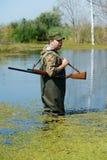 Jäger mit Gewehrgewehr im Sumpf Lizenzfreies Stockfoto