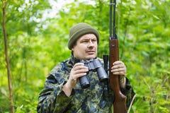 Jäger mit optischem Gewehr und Ferngläsern Stockfotografie