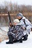 Jäger mit seinem Sohn auf dem Flussufer lizenzfreies stockbild