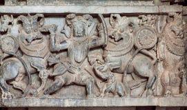 Jäger tötet Löwen auf der Jagd, geschnitzte Skulptur auf historischer Wand des indischen Steintempels Hoysaleswara, Indien Lizenzfreie Stockfotografie