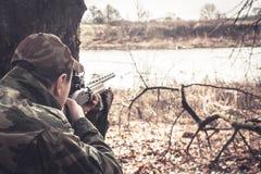 Jägermann mit dem Gewehr und vorbereitet, um einen Schuss zielend während der Jagd zu machen Lizenzfreie Stockfotografie