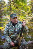 Jägerstillstehen, sitzend auf einem Klotz Lizenzfreie Stockfotografie