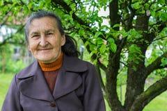 Jährige ältere Plusfrau schöne 80, die für ein Porträt in ihrem Garten aufwirft Stockfoto