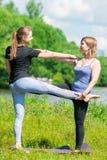 40-jährige Frau mit einem erfahrenen Trainer, der einzeln Yoga tut lizenzfreie stockfotos