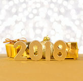 2018-jährige goldene Zahlen auf einem bokeh Hintergrund Stockfotografie