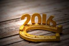 2016-jährige goldene Zahlen mit Hufeisen Stockfoto