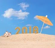 2018-jährige goldene Zahlen mit Muschel auf einem Strand Stockfotografie
