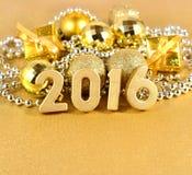 2016-jährige goldene Zahlen und goldene Weihnachtsdekorationen Lizenzfreie Stockbilder