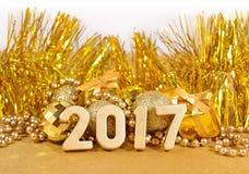2017-jährige goldene Zahlen und goldene Weihnachtsdekorationen Stockfotografie