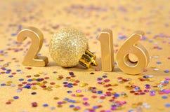 2016-jährige goldene Zahlen und varicolored Konfettis Lizenzfreie Stockfotografie