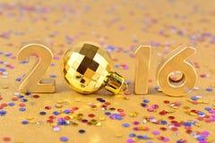 2016-jährige goldene Zahlen und varicolored Konfettis Lizenzfreie Stockfotos