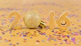 2016-jährige goldene Zahlen und varicolored Konfettis Stockbild