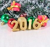 2016-jährige goldene Zahlen und Weihnachtsdekorationen Stockfotografie