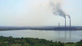 2017-jährige Ukraine Burshtyn-Wärmekraftwerk auf dem Hintergrund des Reservoirs Sonnige Sommertagschwarzrauchverbreitungen stock video footage