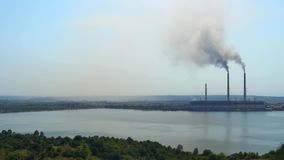 2017-jährige Ukraine Burshtyn-Wärmekraftwerk auf dem Hintergrund des Reservoirs Sonnige Sommertagschwarzrauchverbreitungen stock video