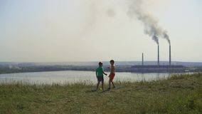 2017-jährige Ukraine Kinderspiel auf dem Hintergrund eines Wärmekraftwerks Sonnige Sommertagschwarzrauchverbreitungen herum stock footage