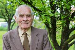 Jähriger älterer Plusmann hübsche 80, der für ein Porträt in seinem Garten aufwirft Stockbilder