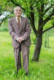 Jähriger älterer Plusmann hübsche 80, der für ein Porträt in seinem Garten aufwirft Lizenzfreie Stockfotos