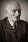 Jähriger älterer Plusmann hübsche 80, der für ein Porträt in seinem Haus aufwirft Stockbild