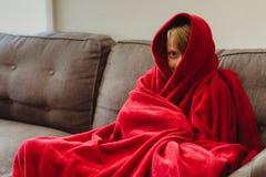 jähriger Junge 8, der auf einer Couch mit einer roten Decke sitzt lizenzfreies stockfoto