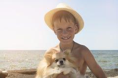 Jähriger Junge glückliche 8, der seine Freundschaft Hund-Pomeranian Shpitz beetwin Leute und Hund umarmt stockbilder