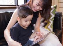 2-jähriger Junge und Mutter, aufpassender Internet-Inhalt mit Tablettengerät stockfoto