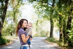 1-jähriges Baby in den Armen der Mutter Stockfotografie