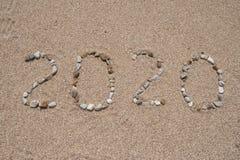 2020-jähriges geschrieben auf den Strandsand stockfotografie