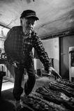 Jähriges Plusporträt des älteren Mannes hübsche 80 Volles Körperschwarzweiss-bild des älteren Mannes im Heizraum, Feuer beginnend Stockfotografie