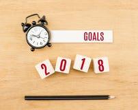 2018-jähriges Rot der Ziele auf hölzernem Würfel mit Draufsicht des Bleistifts und der Uhr Stockbilder