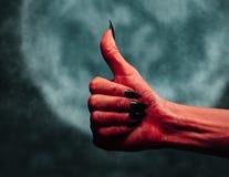 Jäkelhanden med tummen gör en gest upp på midnatt Royaltyfri Fotografi