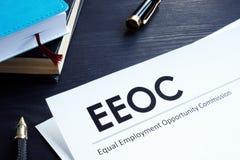 Jämbördigt dokument och penna för sysselsättningstillfällekommission EEOC på en tabell royaltyfri bild