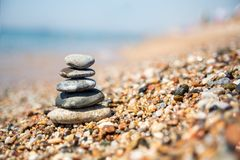 Jämvikt av stenar på stranden, solig dag arkivbilder