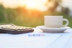 Jämvikt som är skriftlig i bokstavspärlor, och en kaffekopp på tabellen Arkivfoton