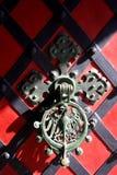 Järn-gjuten dörrknackare med örnen på den röda dörren arkivbilder